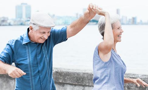 En äldre man och kvinna som dansar och har roligt ute vid stranden med staden i bakgrunden.