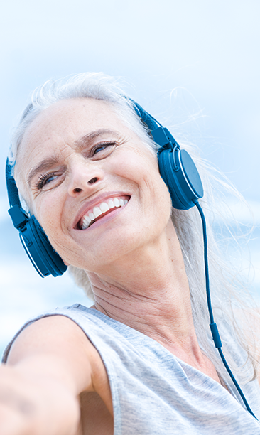 Glad kvinna som lyssnar på musik vid havet och sträcker ut sina armar.